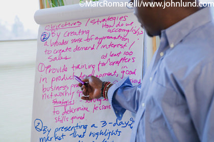 Picture of an African American man pointing at text on flip chart at a business meeting.